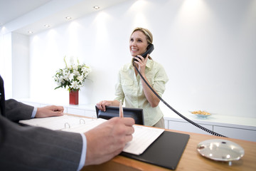 Businessman signing at reception by receptionist on telephone, smiling