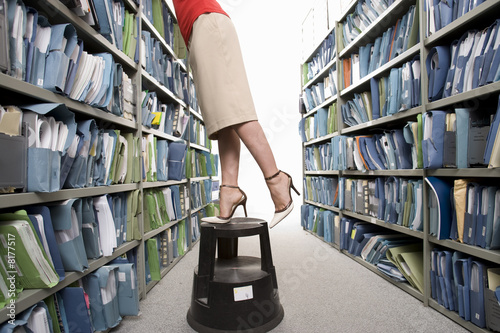 Businesswoman on stool reaching for file, low section