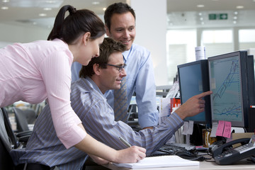 Businessman showing colleagues graph on monitor