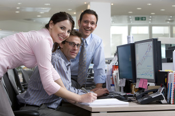Businessman at desk flanked by colleagues, smiling, portrait