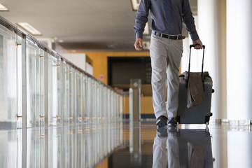 Businessman wheeling luggage in lobby