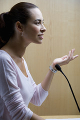 Woman speaking into microphone at conference