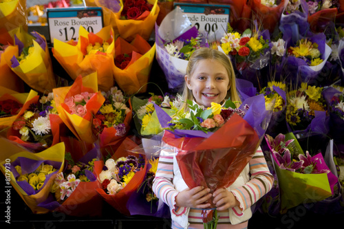 Girl holding bunch of fresh flowers in grocery store