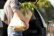 Man loading groceries into rear of car