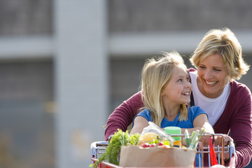 Mother and daughter pushing grocery cart full of groceries