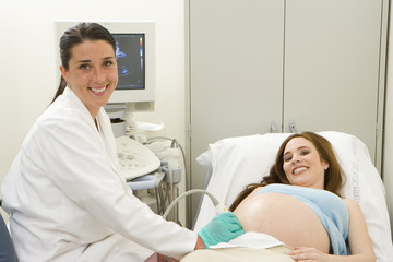 Young woman having pregnancy ultrasound examination