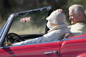 Senior couple on road trip in red convertible