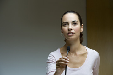 Businesswoman talking into microphone at conference seminar