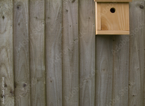 Birdhouse on wooden fence