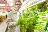 Man choosing carrots in grocery store