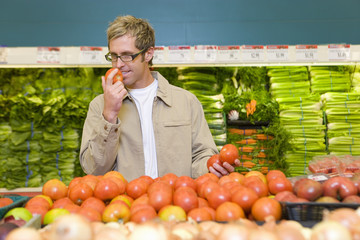 Man choosing tomatoes in grocery store