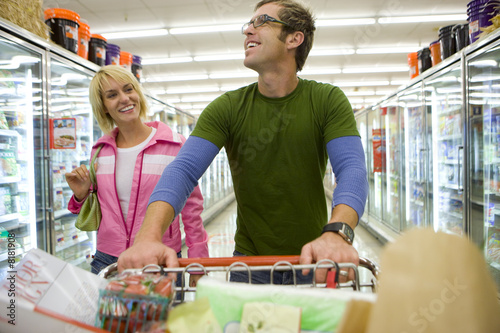Couple grocery shopping in frozen foods section