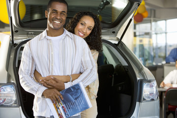 Couple shopping for cars in showroom