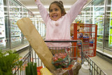 Young girl grocery shopping in frozen foods section