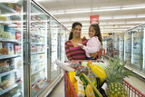 Mother and daughter grocery shopping in frozen foods section