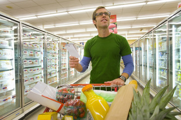 Man grocery shopping in frozen foods section