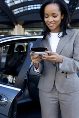 Businesswoman checking text messages on cell phone