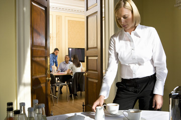 Woman making tea, man and women at table in next room, view through doors