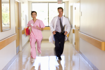 Doctor and nurse running in ward, portrait (blurred motion)