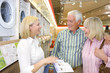 Mature couple in appliance shop smiling at shop assistant with brochure