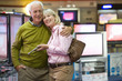 Mature couple arm in arm, shopping for television, smiling, portrait