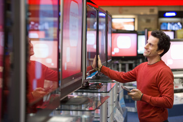 Young man shopping for television, smiling, side view