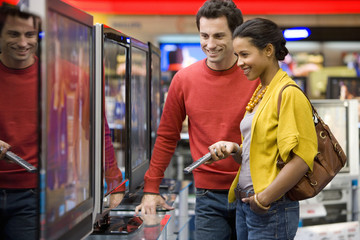 Young couple shopping for television, smiling, side view