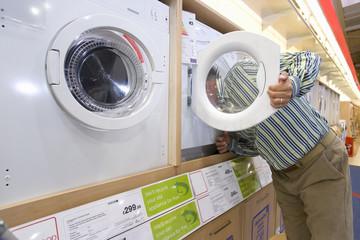 Man shopping, head in washing machine, side view