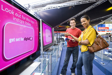 Young couple shopping for television, smiling, low angle view