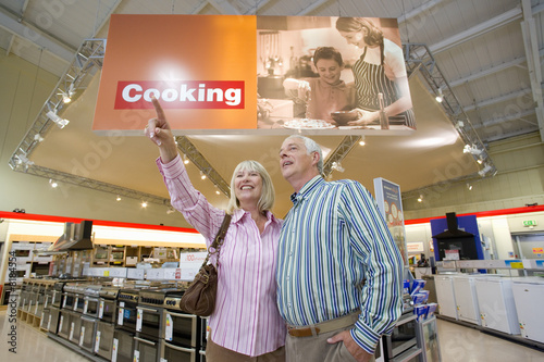 Mature couple shopping in appliance store, woman pointing, low angle view