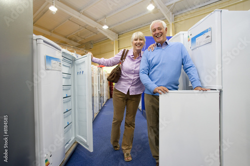 Mature couple shopping for appliances, smiling portrait, low angle view