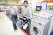 Young couple shopping for washing machine, smiling, portrait