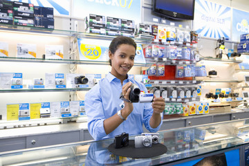 Young saleswoman with video camera, smiling, portrait, low angle view