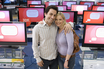 Young couple arm in arm in electronics shop, smiling, portrait, elevated view