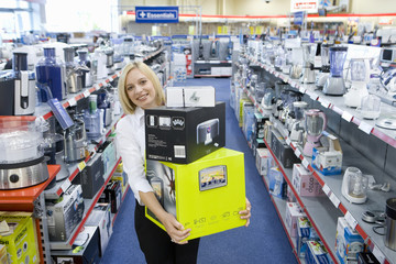 Young woman with boxes in electronics shop, smiling, porttrait