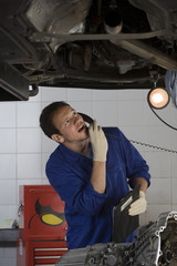 Mechanic on telephone looking at engine of elevated car