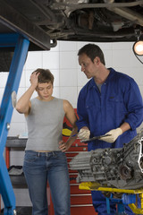 Woman with hand to head by mechanic with clipboard by elevated car