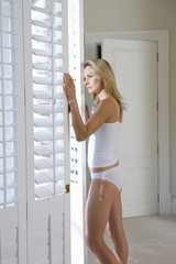 Young woman in underwear peering outdoors, side view