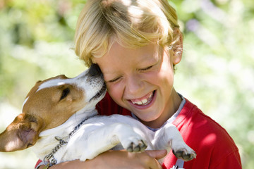 Girl (6-8) embracing dog outdoors, smiling, close-up