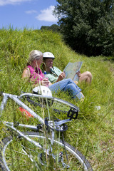 Couple in grass with map by bicycles
