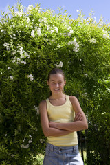 Girl (10-12) with arms crossed by hedge, smiling, portrait