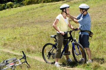 Couple with bicycles in countryside, man adjusting woman's helmet