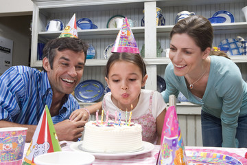 Girl (5-7) blowing out candles of birthday cake, flanked by parents smiling