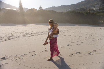Mother walking on beach with baby girl (12-15 months), (lens flare)