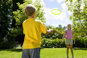 Boy (9-11) and friend playing with flying disc in garden