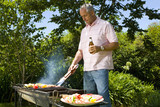 Man using barbeque in garden, low angel view