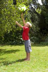 Boy (9-11) retrieving flying disc from tree in garden