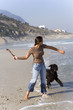Woman preparing to throw stick for dog on beach