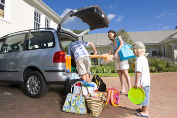 Family of three loading car with luggage, low angle view
