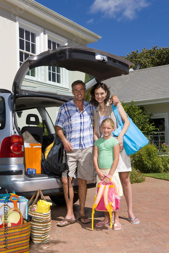 Family of three by luggage and open boot of car, smiling, portrait